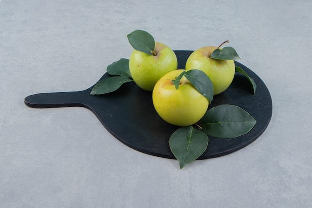 Три свежих яблока на черной деревянной доске.