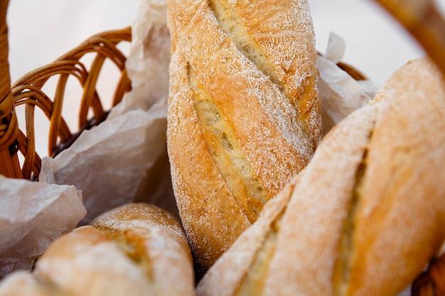 Three fresh baguettes lie in a wicker basket