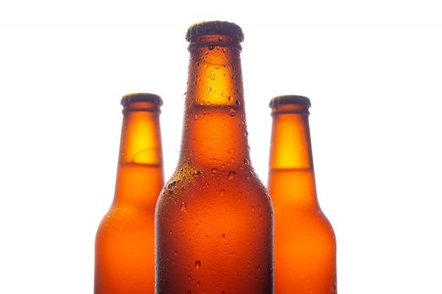 Три бутылки свежего пива с большими каплями воды на белой стене