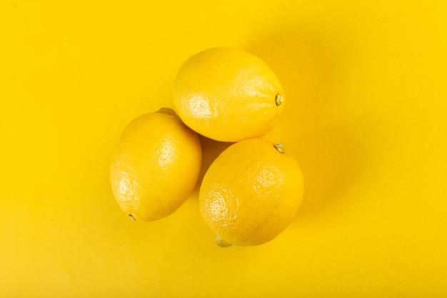 Три свежих ярких лимона на желтом