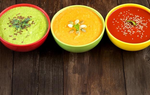 3つの新鮮なカラフルな野菜スープ-木製のテーブルにトマト、カボチャ、グリーンピースをクローズアップ
