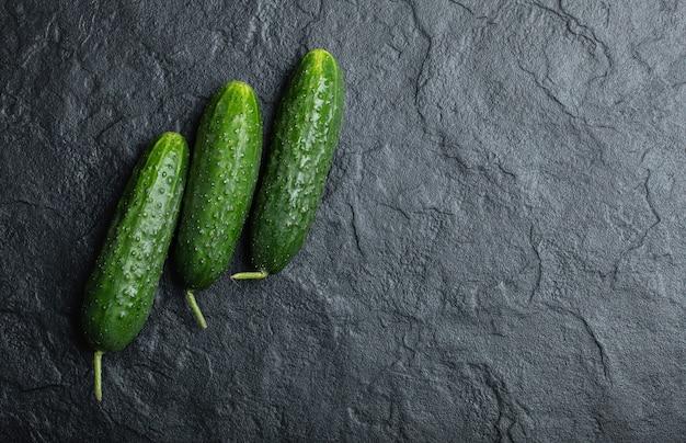 Tre cetrioli freschi su sfondo nero. verdura biologica fresca.