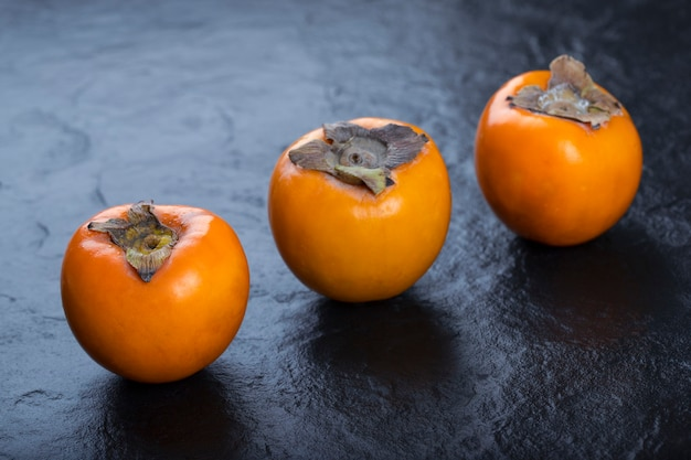 Three fresh fuyu persimmons placed on black surface.