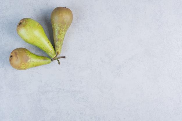 Tre pere verdi fresche su sfondo grigio.