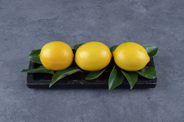 黒い木の板に3つの新鮮なレモンと葉。