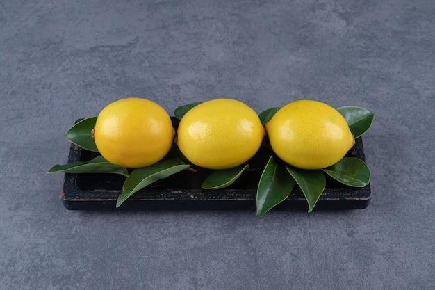 Tre limone fresco e foglie sul bordo di legno nero.