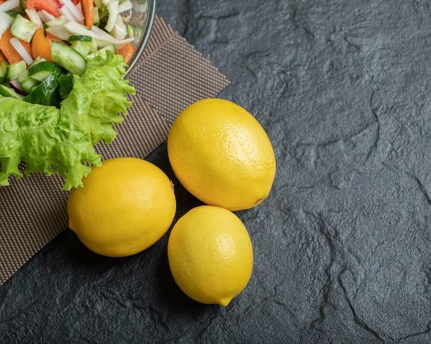 野菜サラダと3つの新鮮なレモン。高品質の写真