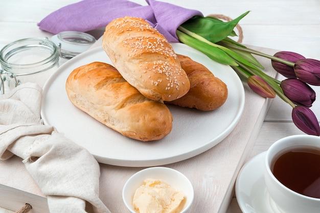 Три свежих хлеба на праздничном фоне с чаем и тюльпанами. вид сбоку.