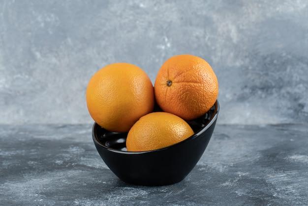 Tre arance fresche in una ciotola nera.