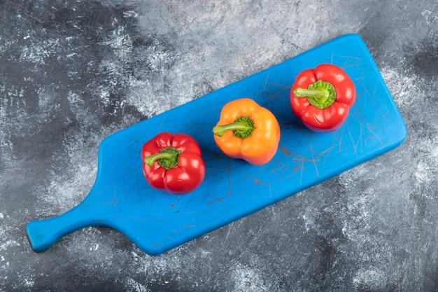 3 свежих органических красочных болгарского перца на голубой разделочной доске.