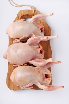 Three fresh organic quails on a wooden board on a white background, top view, vertical format, closeup