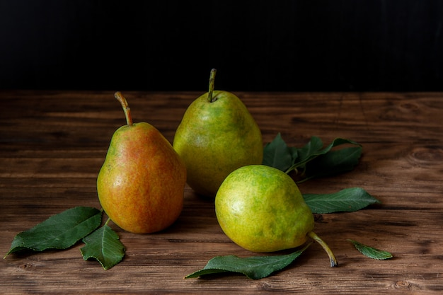 Three fresh pears with leaves lie on a wooden table