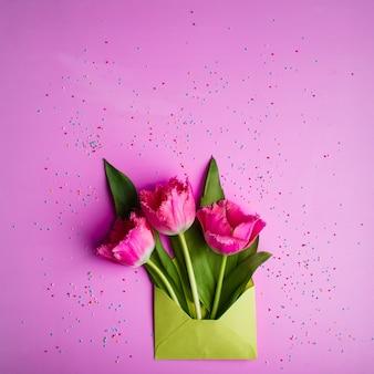 甘い小さな紙吹雪で飾られた薄緑色の封筒の3つの新鮮なピンクのチューリップ。おめでとうのラブレター。春のグリーティングカード。フラットレイ、上面図。