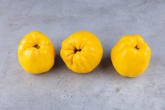 Tre frutti di mela cotogna fresca con spighe di grano poste sul tavolo di pietra.