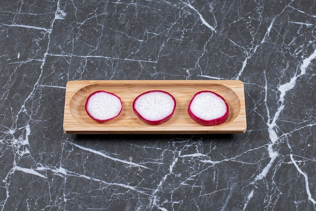 Three fresh radish slices on wooden over black.