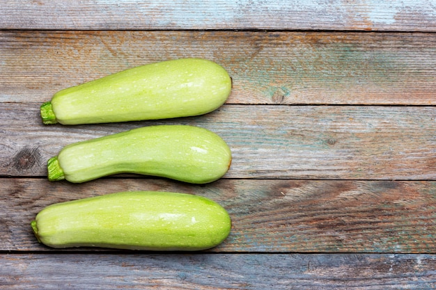Three fresh raw zucchini on an old wooden table with copy space, top view