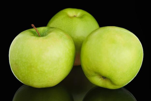 Three fresh ripe green apples on black background