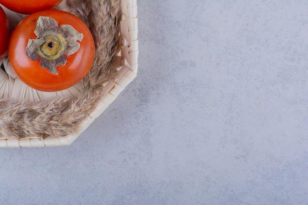 Три свежих спелых плода хурмы в плетеной корзине.