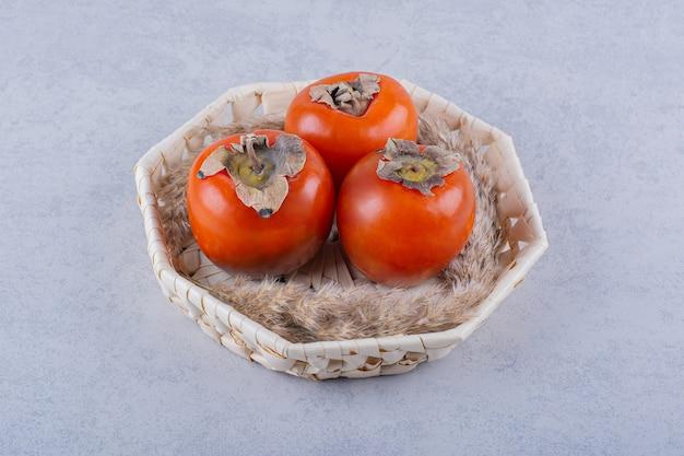 Three fresh ripe persimmon fruits in wicker basket.