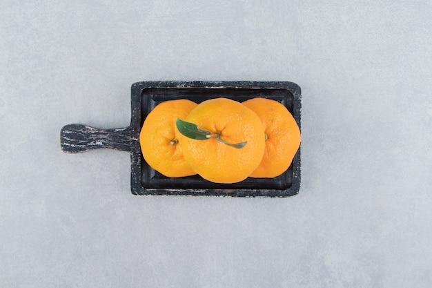 Tre mandarini freschi sul tagliere nero.