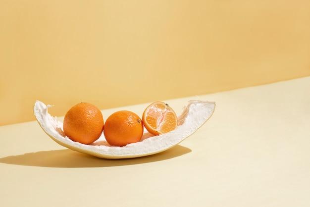Три свежих мандарина на кожуре помело, в солнечном свете, крупным планом. цитрусовые.