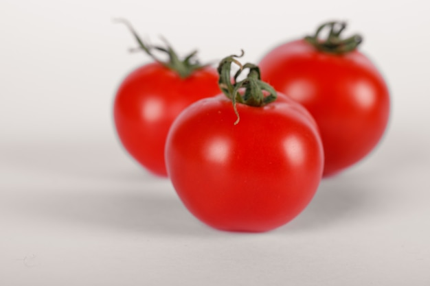 Three fresh tomatoes on white