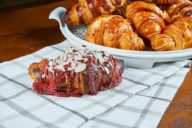 3つの焼きたてのクロワッサン、ストロベリー、チョコレートの木製テーブルの上のベージュの布。ベーカリーカフェの食べ物の写真。ビューを閉じます。