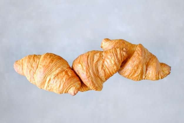 3つの焼きたてのクロワッサンが飛んでいます。テキストのための場所。創造的なパン屋さんのコンセプト。