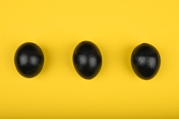 黄色の背景に3つの目玉焼き。フラット横たわっていた。ブラックイースター。 3つの黒い卵