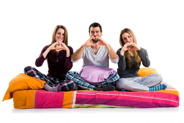 Three friends on a bed making a heart with their hands