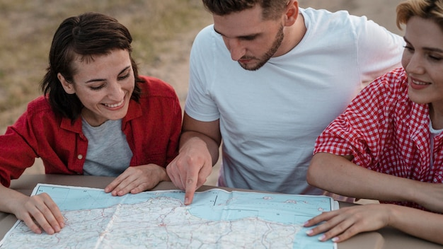 Three friends checking map together while traveling by car