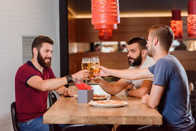 Three friends clinking glasses of beer in pizzeria.