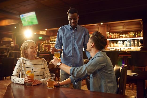 Трое друзей пьют алкоголь и веселятся за столиком в баре. группа людей отдыхает в пабе, ночной образ жизни, дружба, празднование события
