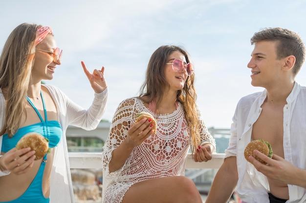 Трое друзей вместе едят гамбургеры на пляже