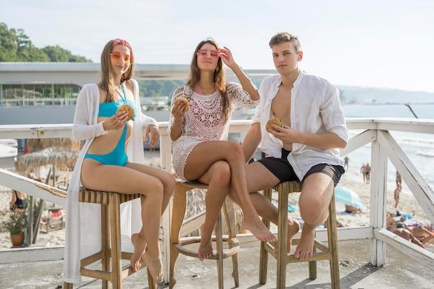 Трое друзей вместе наслаждаются гамбургерами на пляже