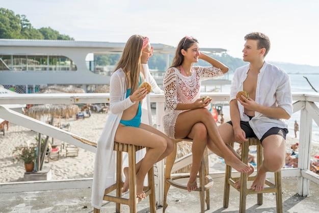 ビーチで一緒にハンバーガーを楽しんでいる3人の友人