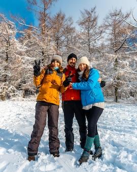 Трое друзей наслаждаются в заснеженном лесу в январе месяце в природном парке артикуца в оярцуне.