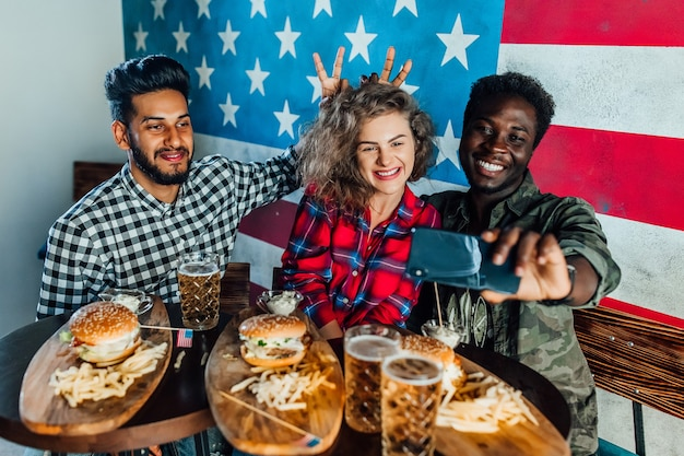 Three friends in fast food restaurant taking selfie while they are eating burgers and drinking beer
