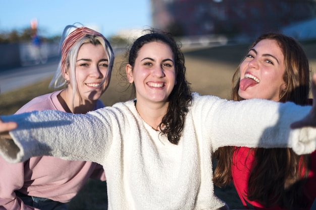Three friends fun girls taking photos with a smartphone at bright sunset.