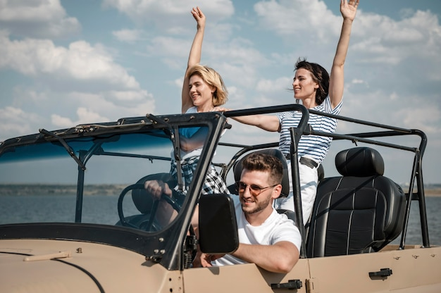 Three friends having fun traveling by car