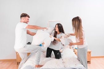 Three friends hitting each other with white pillow on bed