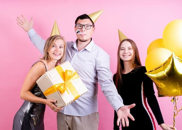 분홍색 배경 위에 생일 파티를 축하하는 생일 모자에 세 친구