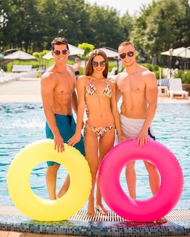 Three friends is posing in swimming pool with rubber rings.