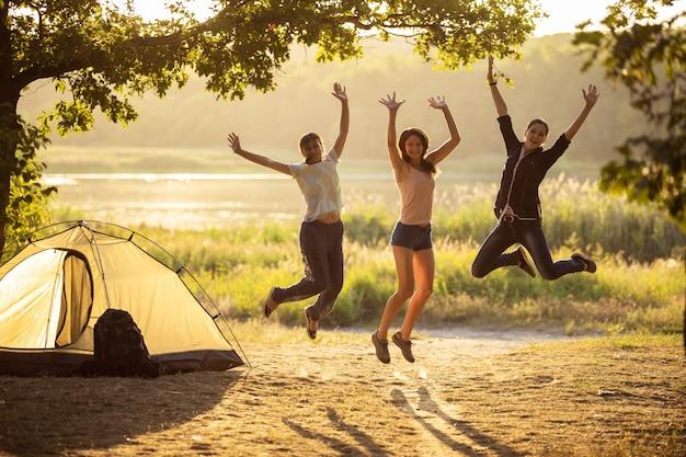 3人の友人が日没時にテントの近くでジャンプします。ハイキングに観光客のグループ