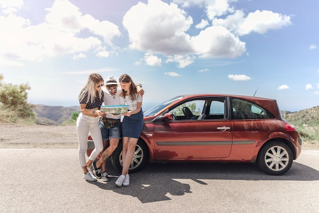 Three friends looking at map standing near the modern car on road