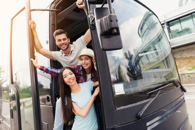 Трое друзей туристов выглядывают из дверей автобуса.