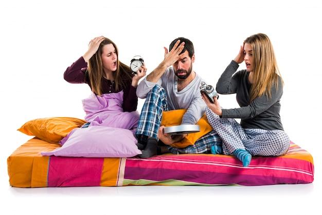 ヴィンテージ時計を持っているベッドの上に3人の友人