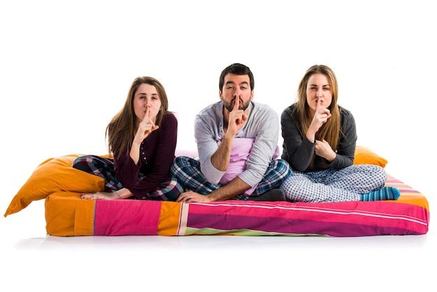 침묵 제스처를 만드는 침대에 세 친구