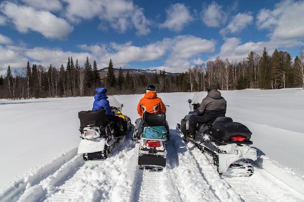 南ウラルの山でスノーモービルに乗っている3人の友人。