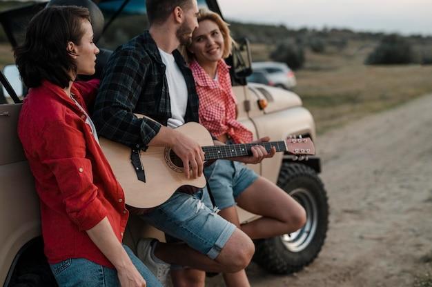Tre amici che suonano la chitarra mentre viaggiano in auto